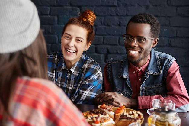 Tiro al coperto di un gruppo interrazziale di tre giovani eleganti che hanno una conversazione facile e vivace