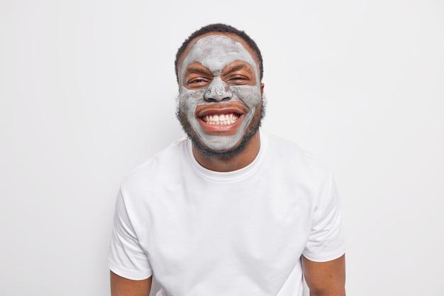 Indoor shot of joyful afro american man grins at camera