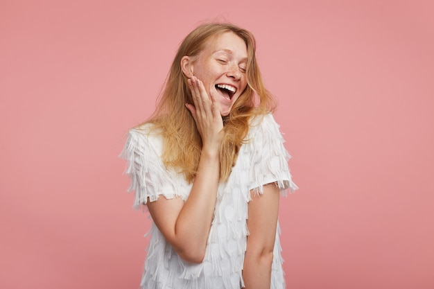 Tiro al coperto di gioiosa attraente giovane signora rossa con acconciatura selvaggia tenendo il palmo sulla sua guancia mentre ride felicemente con gli occhi chiusi, in piedi su sfondo rosa