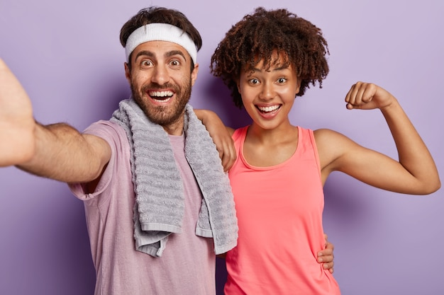 Indoor shot of joyful diverse couple keep muscle flexible, have daily workout, wear sports clothing stand closely look at camera with happy expression