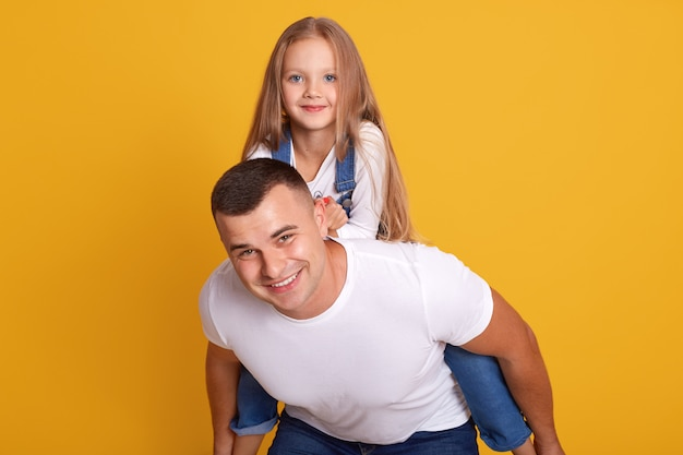 Indoor shot of joyful father giving piggyback ride to his daughter against yellow, happy family wearing casual clothing