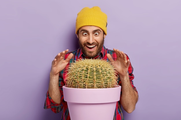 Indoor shot of joyful male florist raises palms over prickly cactus in pot, has surprised happy look, dressed in stylish hat and plait shirt, isolated over purple background. man with indoor plant
