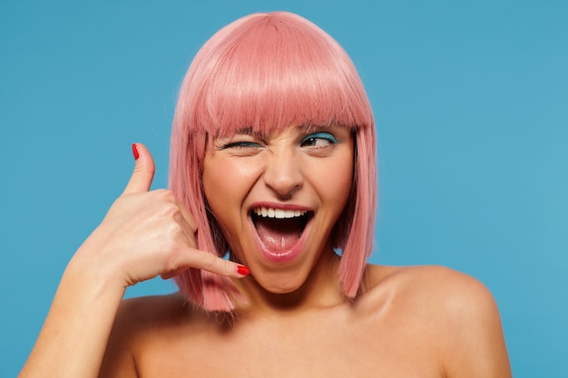 Indoor shot of joyful pretty young female with pink short hair closing one eye while looking aside and keeping her mouth wide opened, raising hand in call me gesture over blue background
