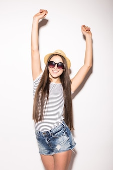 Indoor shot of joyful young european female pretends dancing, wears fashionable blouse, hat and shorts, recreats during summer time, isolated over white wall