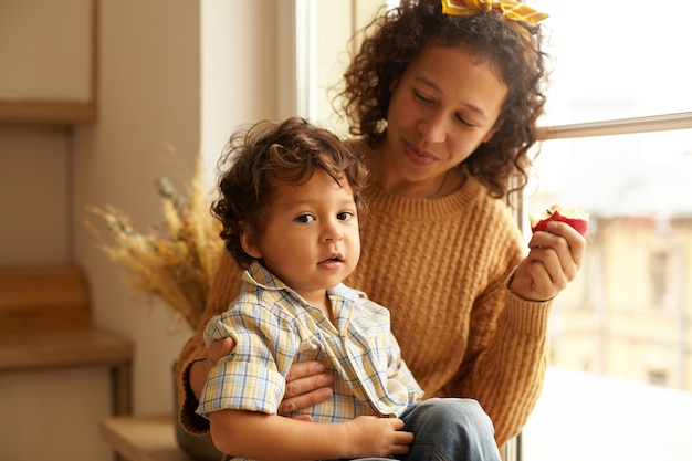 Indoor shot of joyful young female wearing sweater and headscarf eating apple on windowsill with adorable chubby baby boy on her lap. family bonds, relationships, love and parenthood concept