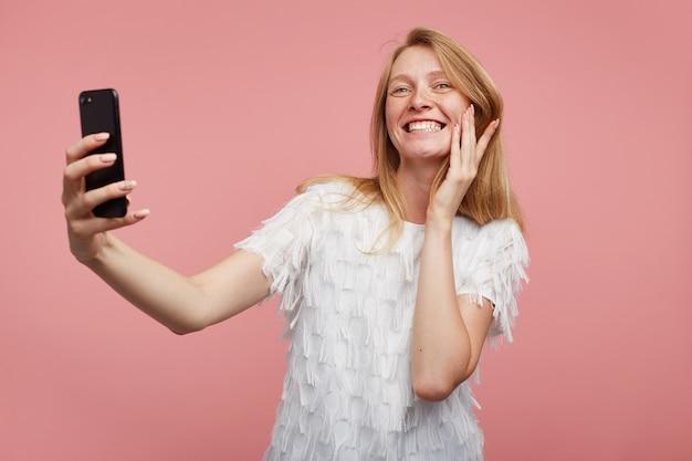 Tiro al coperto di gioiosa giovane femmina adorabile con capelli volpi che mostra i suoi denti bianchi perfetti mentre sorride ampiamente, facendo selfie con il suo smartphone mentre si trova su sfondo rosa