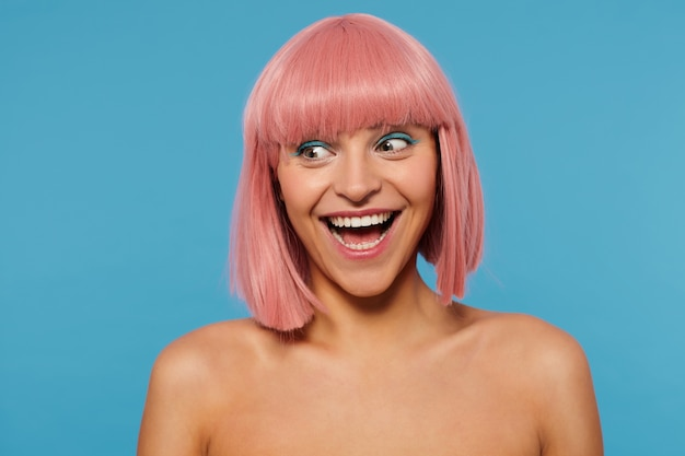 Indoor shot of joyful young lovely woman with pink bob haircut looking exitedly aside and smiling widely, wearing festive makeup while posing over blue background