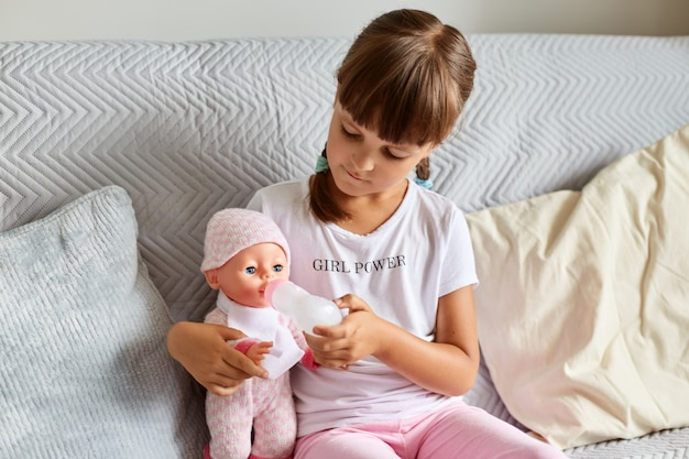 Indoor shot of little girl sitting on the sofa in the room at home playing with baby doll, like mom, dark haired preschooler female child holding toy.