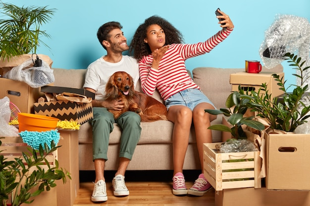 Indoor shot of lovelly family couple make selfie portrait, afro woman blows air kiss in camera of smartphone, pose on comfortable sofa with pet, relocate in new modern apartment, unpack boxes around