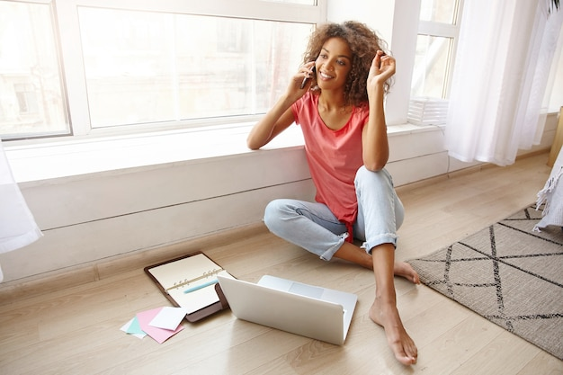Indoor shot of lovely dark skinned lady in pink t-shirt and blue jeans twisting lock of hair on finger, sitting near wide window with crossed legs