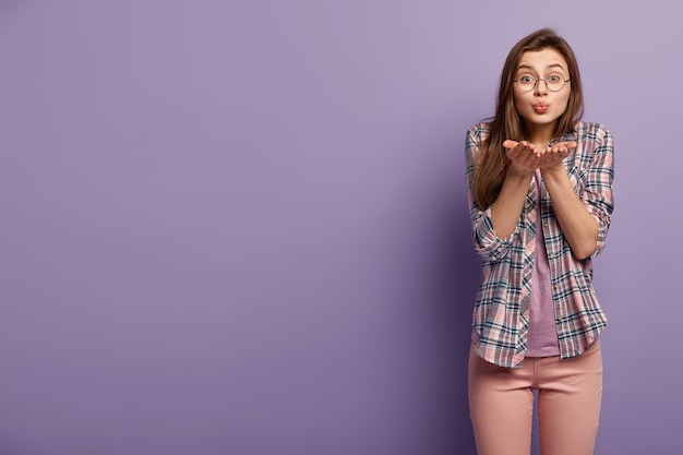 Indoor shot of lovely european woman sends air kiss, keeps lips folded, palms outstretched near mouth
