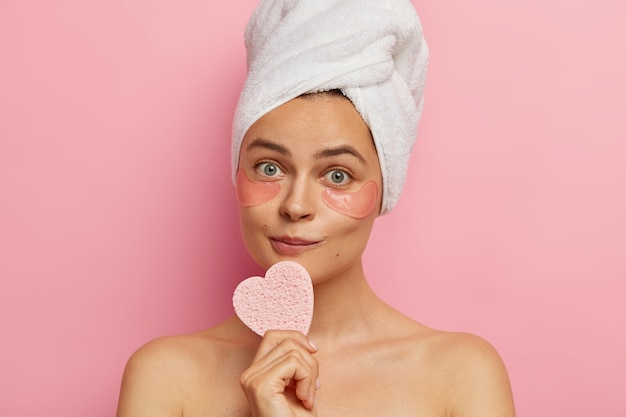 Indoor shot of lovely female has pleasant appearance, healthy fresh skin, holds heart shaped sponge, wears under eye patches for removing fine lines isolated over pink wall. anti aging procedure
