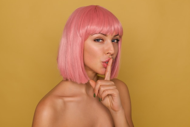 Indoor shot of lovely young blue-eyed pink haired female with natural makeup holding forefinger on her mouth while asking to keep silence, standing over mustard background