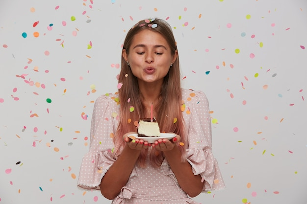 Indoor shot of lovely young long haired blonde woman blowing out candle on birthday cake while standing over white wall, dressed in pink romantic dress