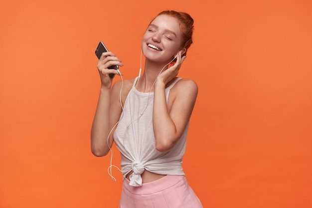 Indoor shot of lovely young woman with foxy bun hairstyle listening favourite music track, holding hand on ear and smiling cheerfully with closed eyes, posing over orange background