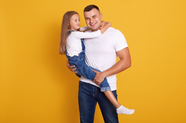 Indoor shot of loving daddy holding at little adorable daughter feeling love isolated over yellow