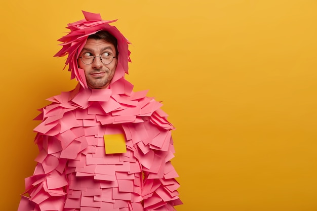 Indoor shot of male advertiser or manager covered with sticky adhesive notes, looks aside as notices something interesting, poses against yellow wall, free space for your advertising content