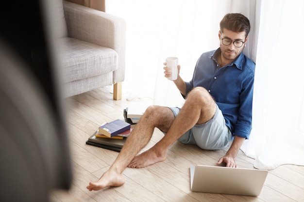 Indoor shot of male nerd student spend all time studying