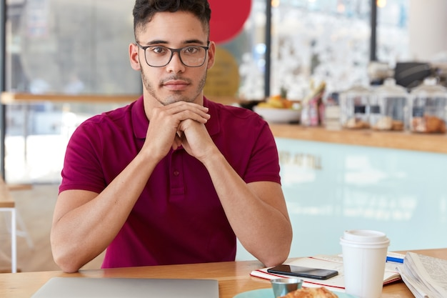 Indoor shot of mixed race man keeps hands under chin, looks with self confident facial expression, wears optical glasses, sits at table in cozy cafeteria, has coffee break after remote work on laptop