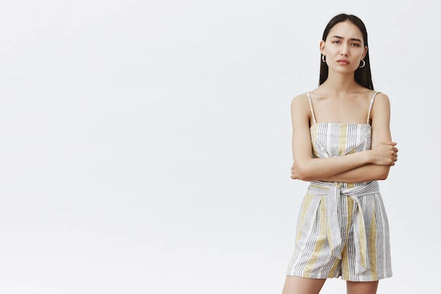 Indoor shot of moody and bossy good-looking asian female model with clean skin and long dark hair, holding hands crossed on chest and frowning, being doubtful and demanding over grey wall