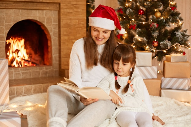 Indoor shot of mother and daughter reading fairy tails in new year eve, woman wearing white sweater and santa claus hat readsbook her charming kid, posing in festive room on floor.
