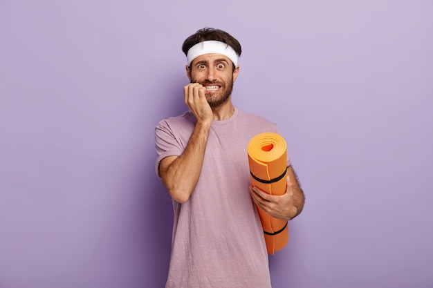 Indoor shot of nervous man bites finger nails, afraids of first yoga class, dressed in active wear, holds mat has training every day
