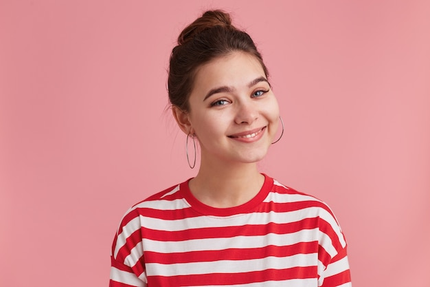 Indoor shot of nice attractive happy young lady, pleasantly smiling looking directly camera, wears striped longsleeve, feels joy and glad, isolated over pink wall.