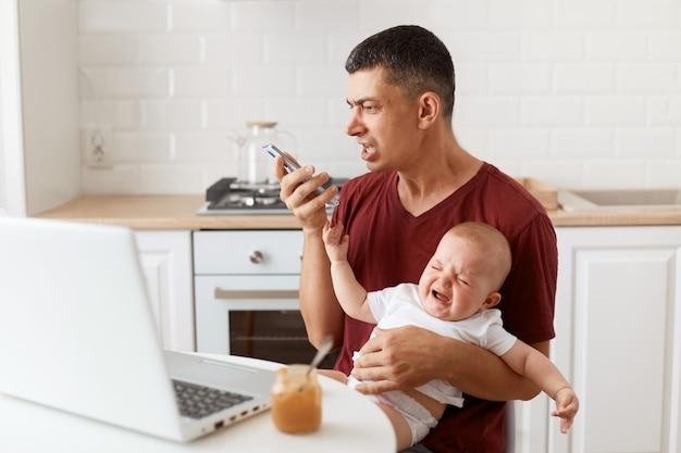 マルーンカジュアルスタイルのtシャツを着て、幼い娘と一緒にキッチンのテーブルに座って、音声メッセージを録音しながら叫んでいる攻撃的な悲しみのブルネットの男性の屋内ショット。