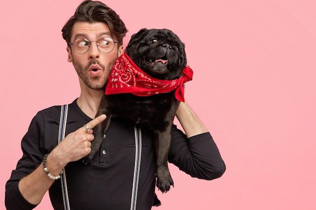 세련된 옷을 입고 어리둥절한 표정으로 놀란 잘 생긴 남성의 실내 촬영은 자신이 좋아하는 강아지와 자유 시간을 보내고 분홍색 벽에 여유 공간을 가리 킵니다. 애완 동물을 가진 남자