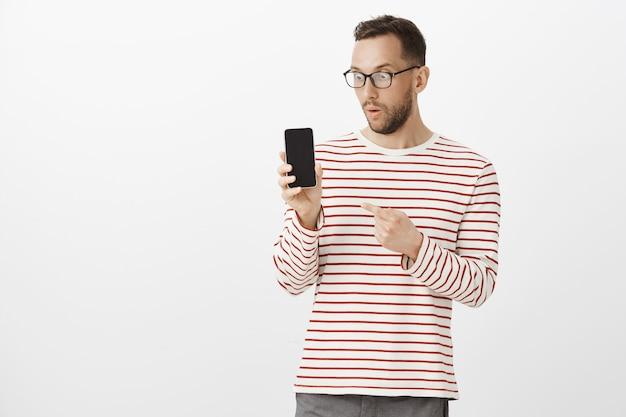 スマートフォンで驚いて感銘を受けた魅力的な男性の室内撮影、スマートフォンを示し、ガジェットを指して見つめる