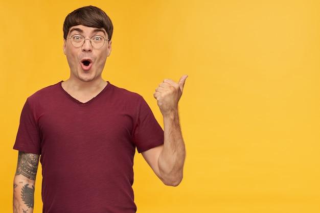 Снимок изумленного позитивного молодого мужчины в помещении, показывающего большим пальцем на место для копирования, с удивленным выражением лица.