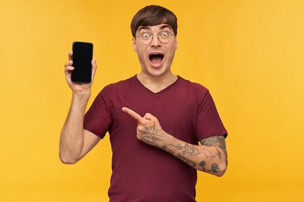 驚いた、ショックを受けた若い男性の屋内ショットは、赤いtシャツを着て、彼の携帯電話の空白の黒いディスプレイを指で指しています