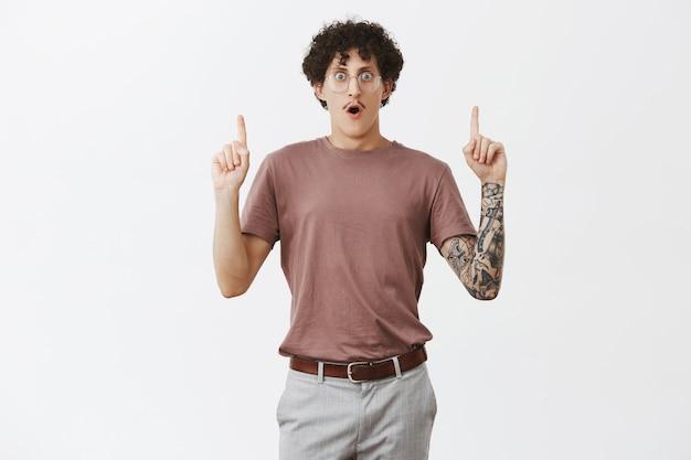 Кадр изумленного безмолвного кудрявого парня в ступоре с усами и татуировками, поднимающего указательные пальцы и указывающего вверх, открывая рот от шока и трепета, видя невероятный шанс