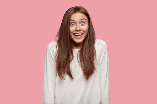 Крытый снимок изумленной молодой кавказской женщины с шокированным удивленным выражением лица