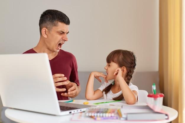 怒っている攻撃的な父親が娘に宿題をするのを手伝いながら叫んでいる様子、家族がテーブルに座って自宅の部屋でポーズをとっている様子の屋内ショット。