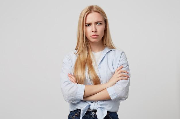 カジュアルな服を着て、しかめっ面を見て、ポーズをとって腕を組んで怒っている若いブロンドの女性の屋内ショット