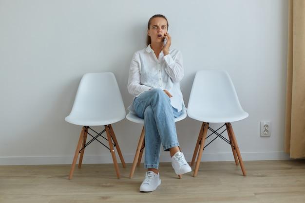 Снимок в помещении: изумленная женщина в джинсах и белой рубашке берет телефон, сидя на стуле, слышит потрясенные новости, удивленное выражение лица, держит рот открытым.