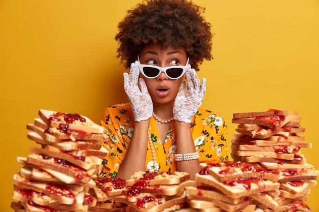 놀란 깜짝 놀란 어두운 피부 여성 모델의 실내 샷은 옆으로 선글라스를 착용하고 레이스 장갑은 보석으로 세련된 옷을 입고 노란색 벽에 고립 된 충격적인 것을 본다