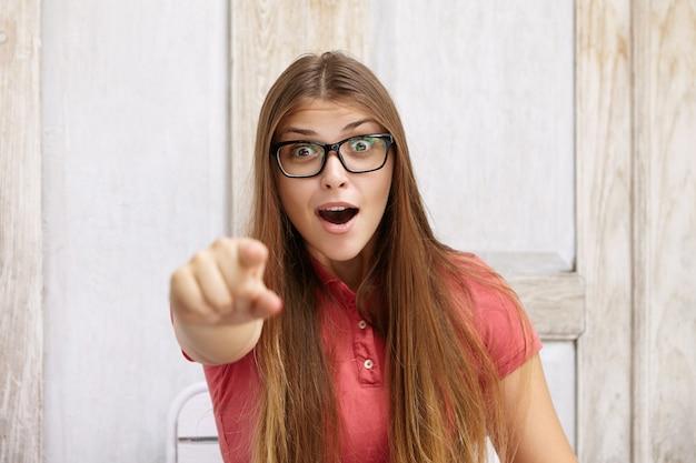 ポロシャツと長方形のメガネを身に着けている驚いた女性の屋内でのショット。驚いたりショックを受けた表情で指を指して、口を大きく開いています。