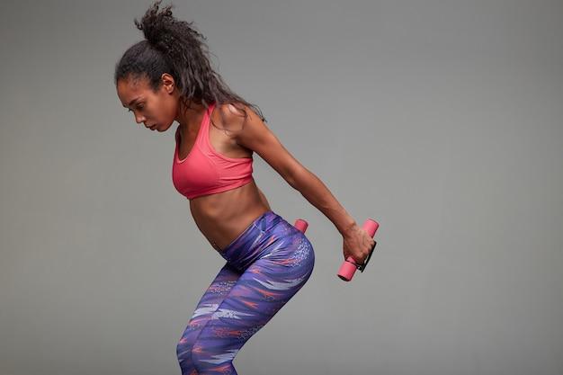 Снимок спортивной молодой темнокожей брюнетки с непринужденной прической, позирующей с утяжелителями в руках. концепция здорового образа жизни