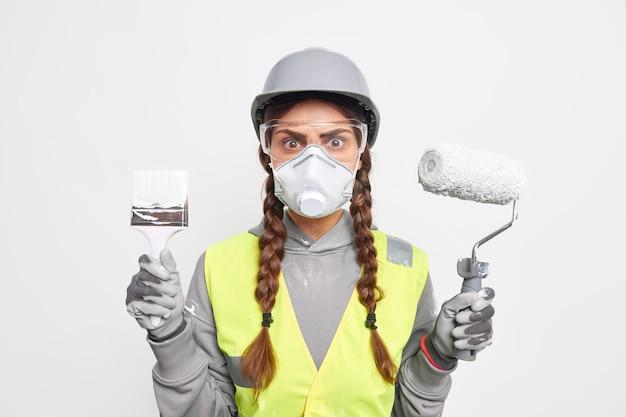 おさげ髪をした気配りのある忙しい女性ビルダーの屋内ショットは、透明な安全メガネを通して然とした表情で、ペイントブラシとローラーを保持し、再建に関与し、保護ヘルメットとフェイスマスクを着用している