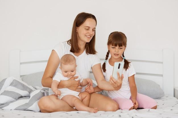 Крытый снимок привлекательной кавказской женщины в белой футболке повседневного стиля, сидящей на кровати со своими двумя дочерьми, держа на руках младенца и позируя с мобильным телефоном в руках.