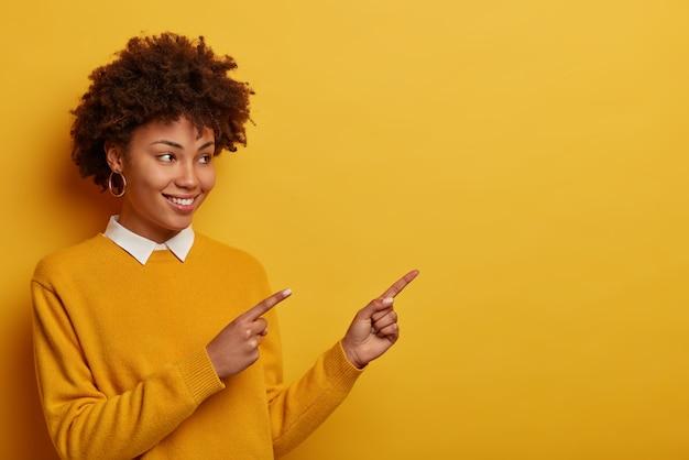 Снимок в помещении: привлекательная кудрявая женщина указывает на верхний правый угол, демонстрирует красивую рекламу на пустом месте, носит аккуратный желтый свитер.