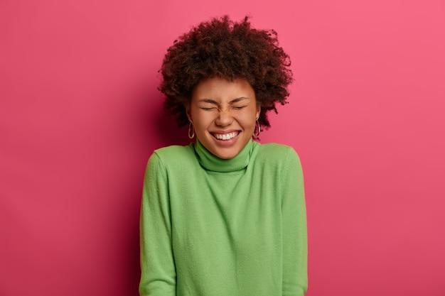 매력적인 곱슬 젊은 여성의 실내 촬영은 넓게 미소 짓고 하얀 치아를 보여주고 재미있는 농담을 웃으며 성실한 감정을 표현하고 분홍색 벽 위에 포즈를 취합니다. peope, 감정, 라이프 스타일 컨셉