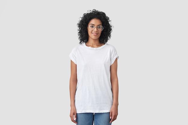 さわやかな髪の魅力的な暗い肌の女性の屋内ショット、丸いメガネをかけ、カジュアルな白いtシャツとジーンズを着て、屋内でポーズをとり、アフロの髪型をしています。
