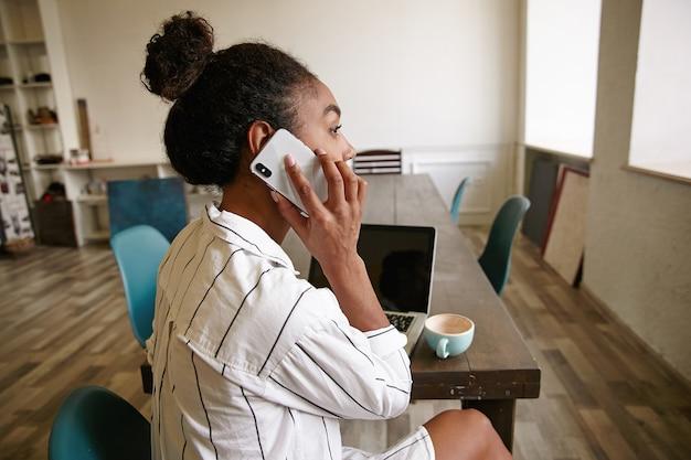Снимок в помещении привлекательной темнокожей женщины с прической в виде пучка, сидящей за длинным деревянным столом, разговаривающей по телефону и задумчиво смотрящей в окно