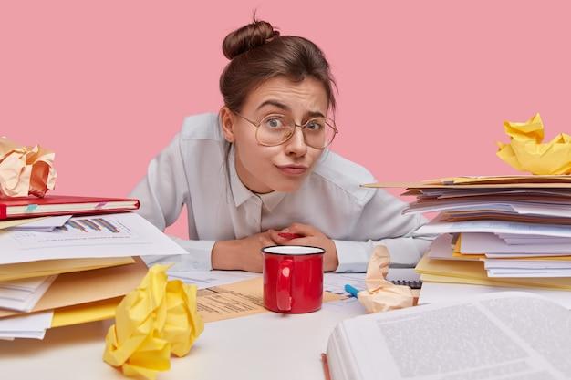 매력적인 유럽 학생의 실내 촬영은 머리 매듭이 있고 좋은 시력을 위해 안경을 착용합니다.