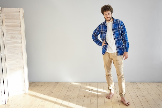 トレンディなベージュのジーンズと格子縞の青いシャツを着て、自宅の木の床に裸足でポーズをとって、腰に手を当てて、魅力的なファッショナブルな若いヨーロッパのひげを生やした男性モデルの屋内ショット