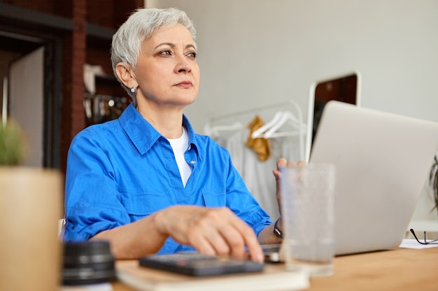 집에 사무실 책상에 앉아 랩톱 컴퓨터를 사용하는 프리랜서로 일하는 매력적인 회색 머리 여성 연금의 실내 샷. 노화, 은퇴, 기술, 여가 및 직업 개념