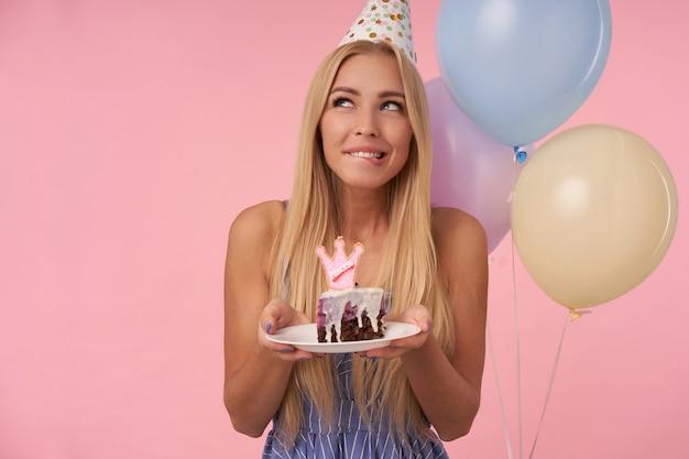 Снимок привлекательной длинноволосой блондинки в помещении, которая радуется, позируя в разноцветных воздушных шарах, держа кусок торта и задумчиво глядя в сторону, кусая нижнюю губу на розовом фоне